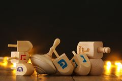 Jewish holiday Hanukkah with wooden dreidels colection & x28;spinning top& x29; and gold garland lights on the table. Image of jewish holiday Hanukkah with Royalty Free Stock Photos