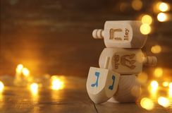 Jewish holiday Hanukkah with wooden dreidels colection & x28;spinning top& x29; and gold garland lights on the table. Image of jewish holiday Hanukkah Stock Photos