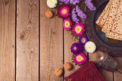 Jewish holiday Passover background with matza, seder plate and spring flowers. Royalty Free Stock Photo