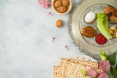 Jewish holiday Passover background with matzo, seder plate and spring flowers stock photography