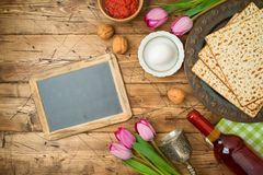 Jewish holiday Passover background with matzo, seder plate, wine, tulip flowers and chalkboard on wooden table stock photos