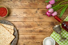 Jewish holiday Passover background with matzo, seder plate, wine and tulip flowers on wooden table royalty free stock photo