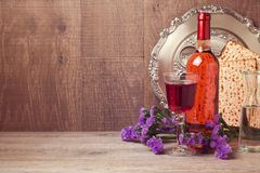 Jewish holiday Passover background with matzoh and wine bottle. Over wooden wall Stock Photography