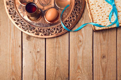 Jewish holiday Passover concept with matzah, seder plate, egg and wine on wooden background. Stock Photography