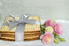 Jewish holiday of Passover and matzo. Jewish holiday of Passover, gift wrap matzo, tied with a ribbon and a bouquet of peonies stock image