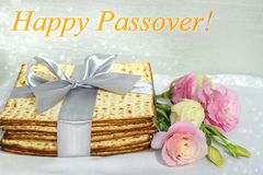 Jewish holiday of Passover and matzo. Jewish holiday of Passover, gift wrap matzo, tied with a ribbon and a bouquet of peonies, inscription - Happy Passover stock images