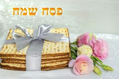 Jewish holiday of Passover and matzo. Jewish holiday of Passover, gift wrap matzo, tied with a ribbon and a bouquet of peonies, inscription in hebrew - Happy stock photography