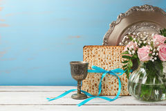 Jewish holiday Passover Pesah background with matzoh, rose flowers and wine glass on wooden table Royalty Free Stock Images