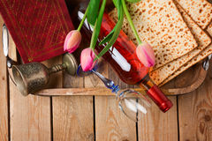 Jewish holiday Passover Pesah celebration with matzoh, tulip flowers and wine bottle on wooden background. Royalty Free Stock Photography
