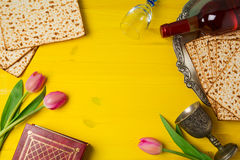 Jewish holiday Passover Pesah celebration with matzoh, tulip flowers and wine bottle on yellow wooden background. Stock Photos