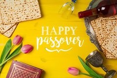 Jewish holiday Passover Pesah celebration with matzoh, tulip flowers and wine bottle on yellow wooden background. View from above Royalty Free Stock Images