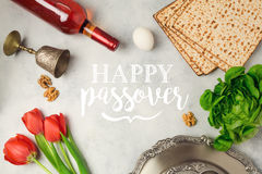 Jewish holiday Passover Pesah greeting card with seder plate, matzoh and red wine bottle. Stock Photo