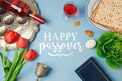 Jewish holiday Passover Pesah greeting card with seder plate, matzoh, tulip flowers and wine bottle on wooden background. Royalty Free Stock Photos