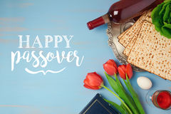 Jewish holiday Passover Pesah greeting card with seder plate, matzoh and tulip flowers on wooden rustic background stock photo