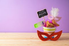 Jewish holiday Purim background with bucket, carnival mask, noisemaker and hamantaschen cookies on wooden table. Creative Purim basket idea stock images