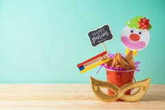 Jewish holiday Purim background with bucket, carnival mask, noisemaker and hamantaschen cookies on wooden table. Creative Purim basket idea royalty free stock photography