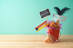 Jewish holiday Purim background with bucket, carnival mask, noisemaker and hamantaschen cookies on wooden table. Creative Purim basket idea royalty free stock images