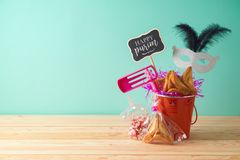 Jewish holiday Purim background with bucket, carnival mask, noisemaker and hamantaschen cookies on wooden table. Creative Purim basket idea royalty free stock photos