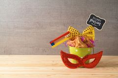 Jewish holiday Purim background with bucket, carnival mask, noisemaker and hamantaschen cookies on wooden table. Creative Purim basket idea stock image
