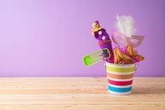 Jewish holiday Purim background with bucket, carnival mask, noisemaker and hamantaschen cookies on wooden table. Creative Purim basket idea stock photo