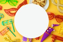 Jewish holiday Purim background with carnival mask, noisemaker and hamantaschen cookies. Top view from above. Flat lay royalty free stock photography