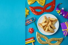 Jewish holiday Purim background with carnival mask, noisemaker and hamantaschen cookies. Top view from above. Flat lay stock photo
