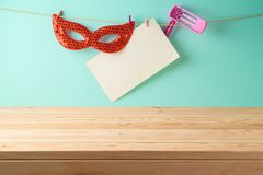 Jewish Holiday Purim holiday background with empty wooden table, paper note, carnival mask and noisemaker toy. Jewish Holiday Purim holiday background with empty royalty free stock photos