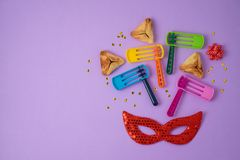 Jewish holiday Purim background with hamantaschen cookies, noisemaker and carnival mask. Top view from above. Flat lay royalty free stock images