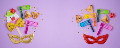 Jewish holiday Purim background with hamantaschen cookies, noisemaker and carnival mask. Top view from above. Flat lay stock images