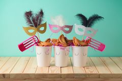Jewish holiday Purim background with paper cup, carnival mask, noisemaker and hamantaschen cookies on wooden table. Creative Purim basket idea stock images