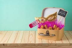 Jewish holiday Purim background with suitcase box, carnival mask, noisemaker and hamantaschen cookies on wooden table. Creative Purim basket idea stock photography