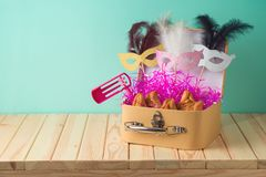 Jewish holiday Purim background with suitcase box, carnival mask, noisemaker and hamantaschen cookies on wooden table. Creative Purim basket idea stock images