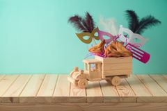 Jewish holiday Purim background with toy truck, carnival mask, noisemaker and hamantaschen cookies. On wooden table. Creative Purim basket idea royalty free stock photo