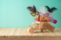 Jewish holiday Purim background with toy truck, carnival mask, noisemaker and hamantaschen cookies on wooden table. Creative Purim basket idea royalty free stock image