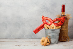 Jewish holiday Purim concept with hamantaschen cookies or hamans ears, carnival mask. And wine bottle Stock Photo