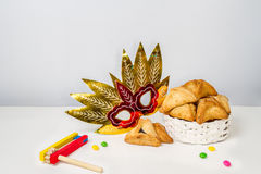 Jewish holiday of Purim. Hamantaschen cookies, gragger and carnival mask Stock Photos