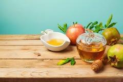 Jewish holiday Rosh Hashana background with honey jar, apple and pomegranate on wooden table Royalty Free Stock Image