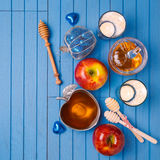 Jewish holiday Rosh Hashana still life with honey, apples and candles on wooden blue table. View from above. Stock Images