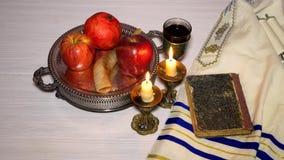 Rosh hashanah jewish holiday concept shofar, torah book, honey, apple and pomegranate. traditional holiday symbols. Jewish holiday shofar, torah book, honey stock footage