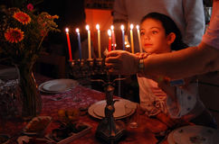 Jewish Holidays Hanukkah. A family is lighting a candle for the Jewish holiday of Hanukkah stock images