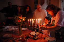 Jewish Holidays Hanukkah. A family is lighting a candle for the Jewish holiday of Hanukkah. Hanukkah or Chanukah, Chanukkah, or Chanuka, also known as the royalty free stock image