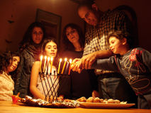 Jewish Holidays Hanukkah. A family is lighting a candle for the Jewish holiday of Hanukkah royalty free stock photos