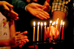 Jewish Holidays Hanukkah. A family is lighting a candle for the Jewish holiday of Hanukkah that is observed for eight nights and days stock photos