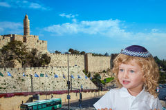The Jewish little boy stands against castle walls of Jerusalem Stock Photo