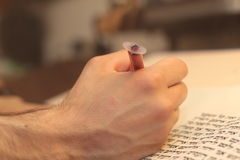 Jewish man with beard writing on a parchment scroll. Photo taken on: December 30th,2015. A sacred roll which write manually Royalty Free Stock Photo