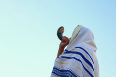 Jewish man blowing the Shofar (horn) of Rosh Hashanah (New Year). Religious symbol royalty free stock image