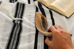 Jewish man hands next to Prayer book, praying, next to tallit. Jewish traditional symbols. Rosh hashanah jewish New Year holiday. Shabbat and Yom kippur stock photography