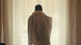 Jewish man praying in home. Back of Jewish man in robe praying next to sunny window in home stock video