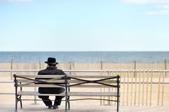 Jewish man sitting on bench near ocean Royalty Free Stock Photos