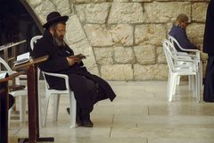 Jewish man sitting on a chair and holding bible book, praying at the sacred Wailing Wall, Western Wall, Jerusalem royalty free stock images